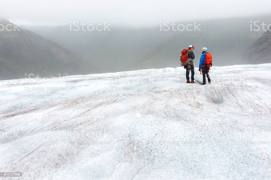 Two guides discuss route on icy glacier stock photo