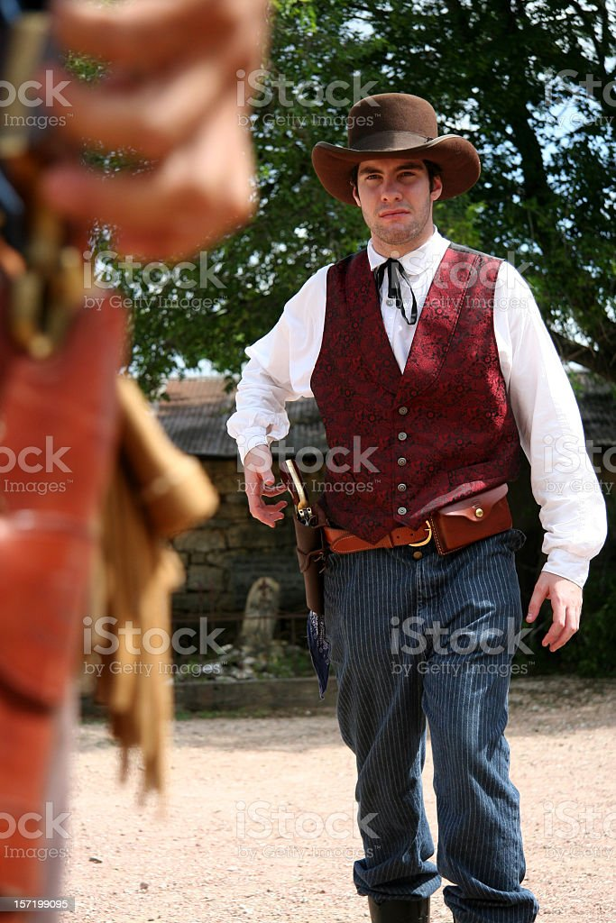 Two Gunslingers Face Off In Middle Of A Dirt Road stock photo