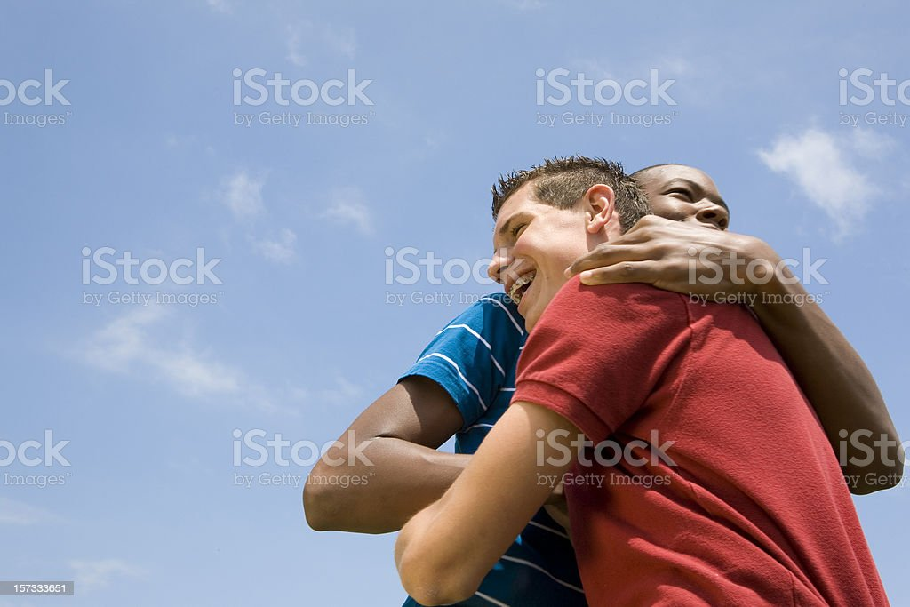 Two Guy Friends Hugging One Another Under The Blue Sky stock photo