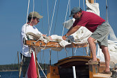 Two guy getting sail boat ready for sailing