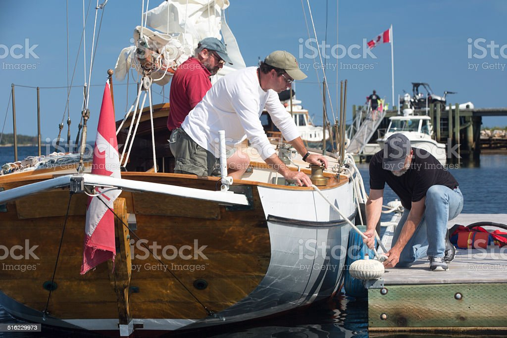 Two guy getting sail boat ready for sailing stock photo