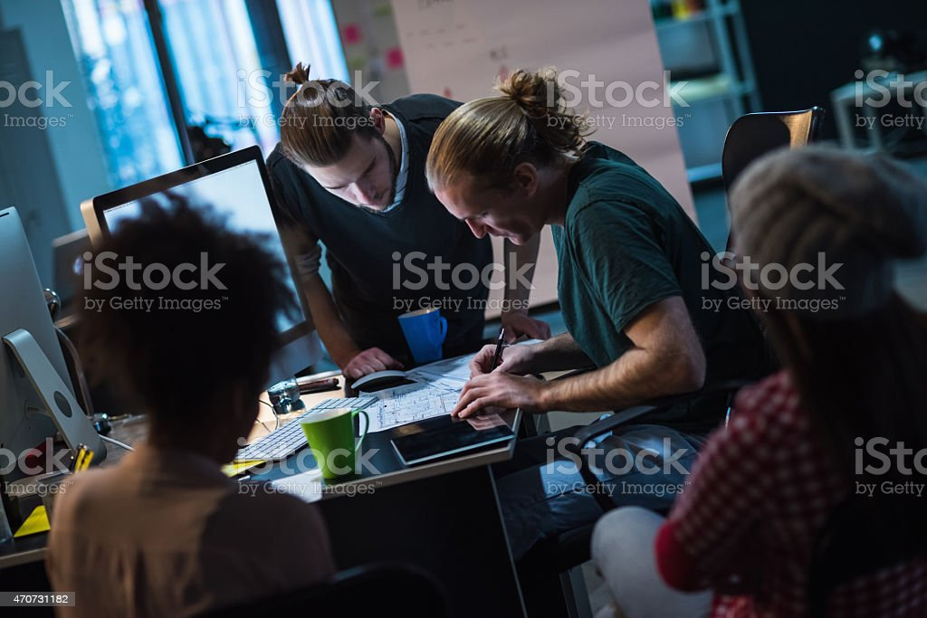 Two guys and girls working on a project and drinking coffee stock photo