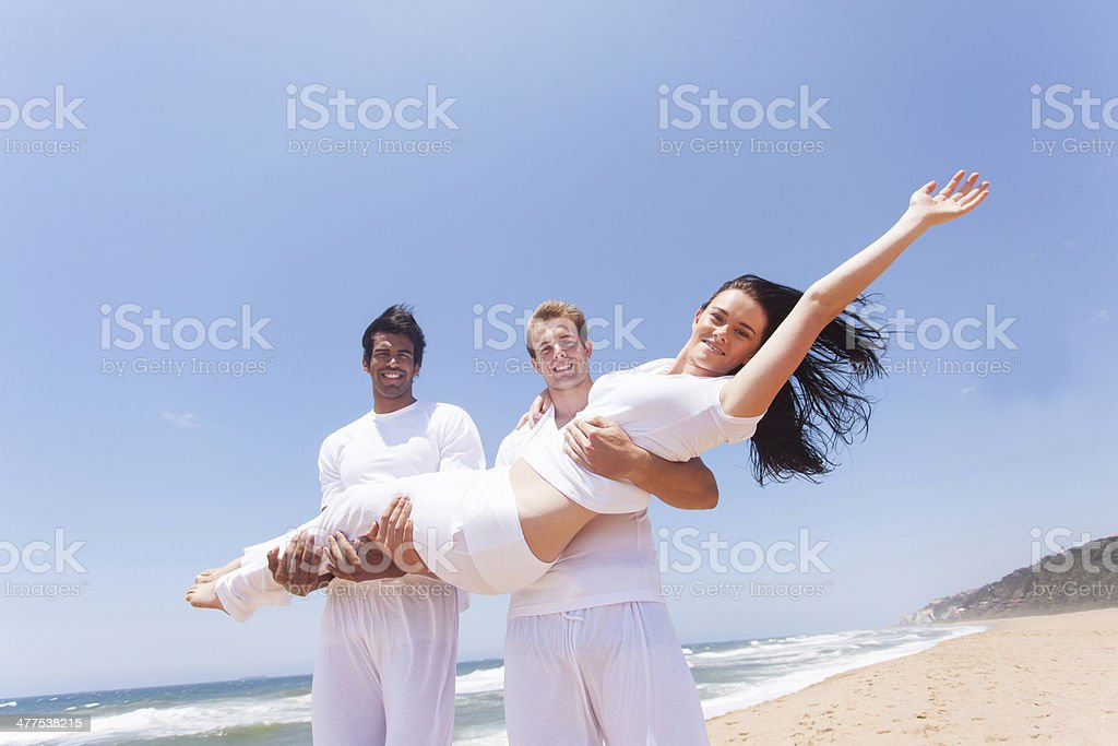 two guys carrying a girl on beach royalty-free stock photo