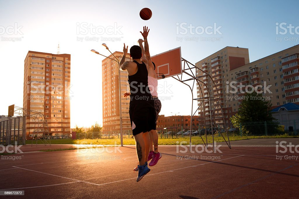 Two guys jump stretch to the ball near the ring stock photo