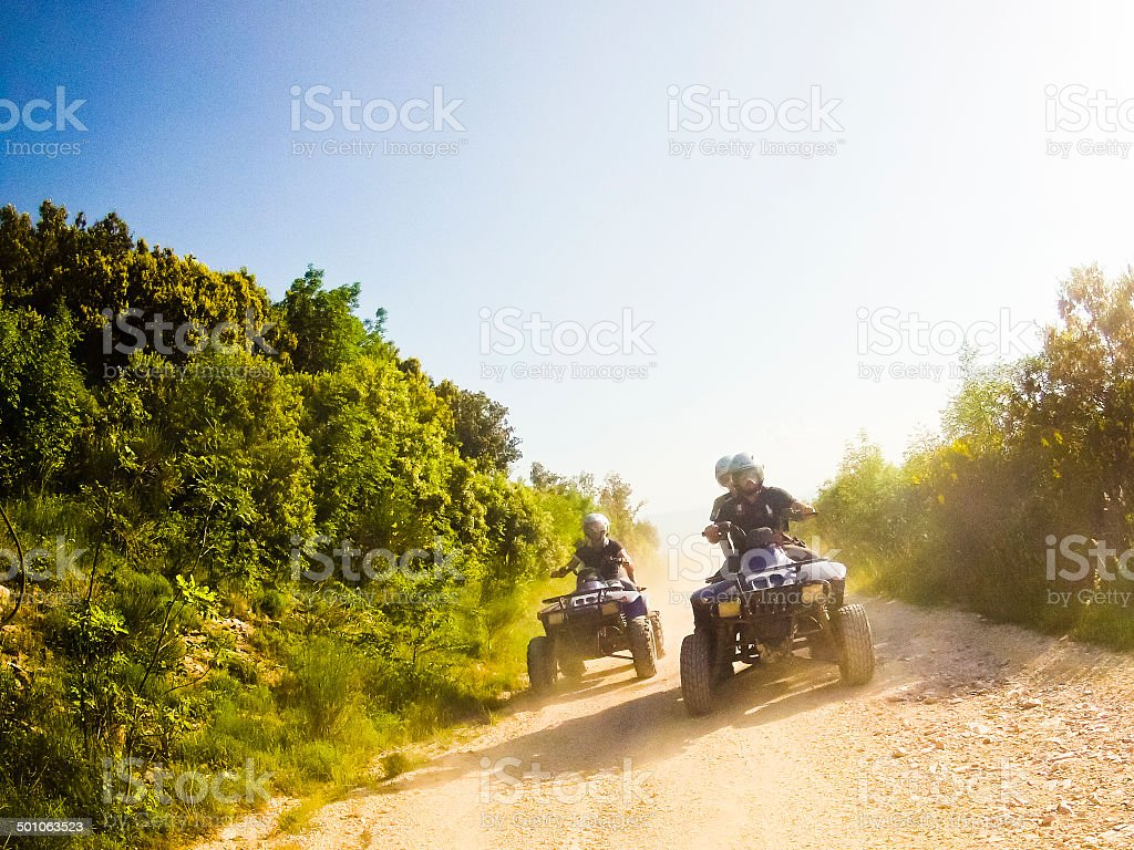 two guys on quad bikes in mountain trail stock photo