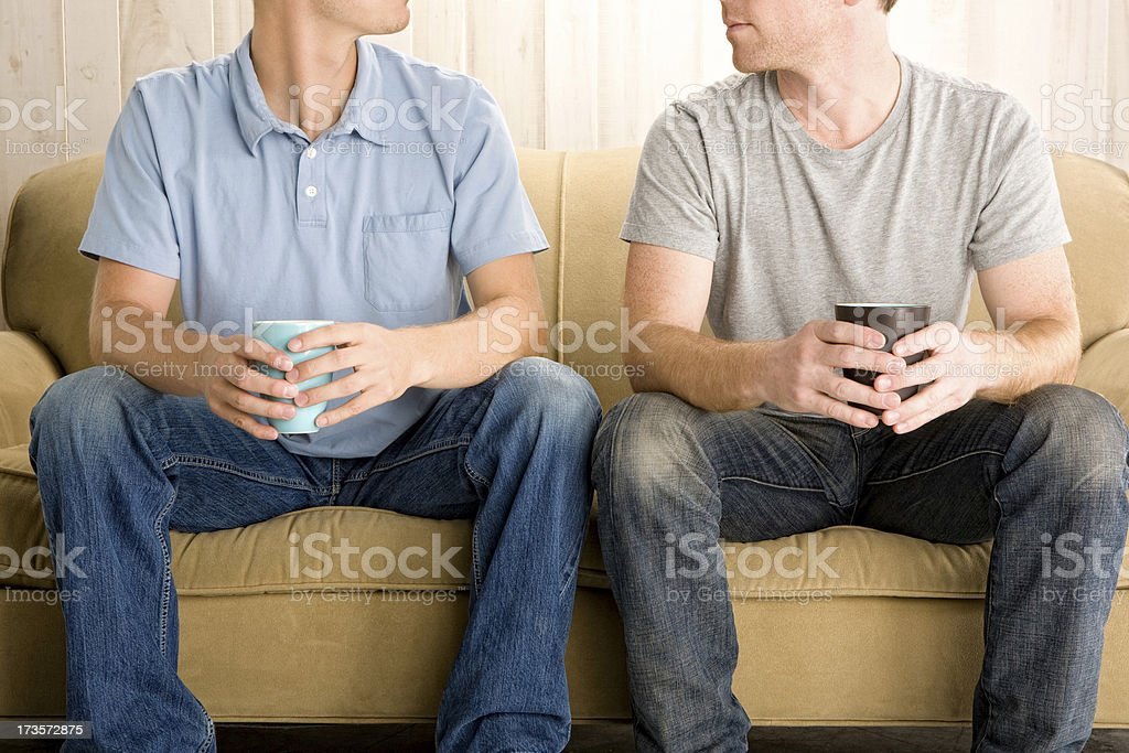 Two guys sitting on a couch stock photo