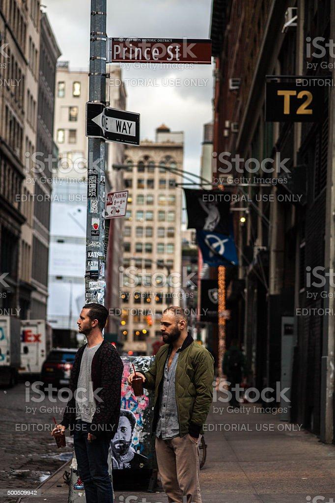 Two guys with drinks on Prince street, soho. NYC. stock photo