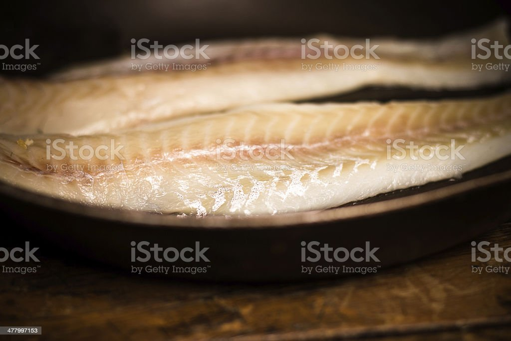 Two haddock fillets in frying pan royalty-free stock photo