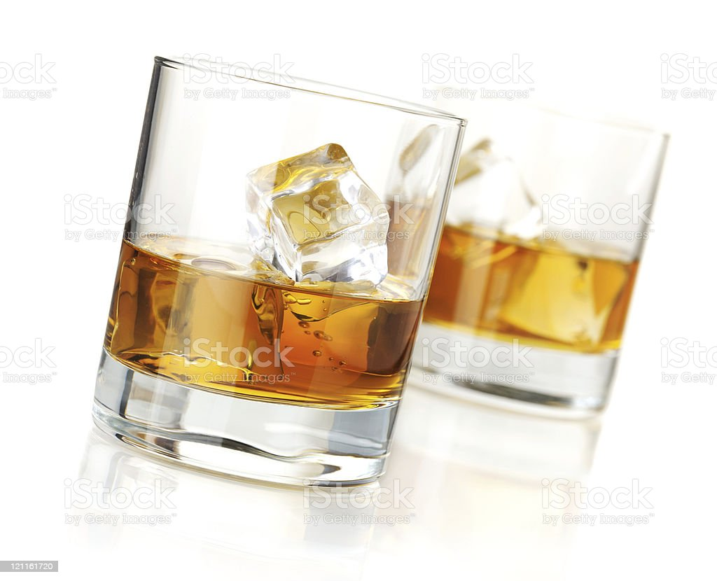 Two half full glasses of whiskey on the rocks royalty-free stock photo