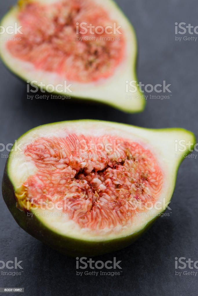 Two halves of a fresh fig on a dark baseboard stock photo