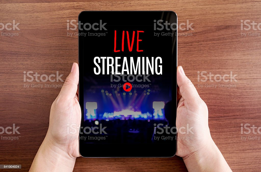 Two hand holding tablet with Live streaming and play icon stock photo