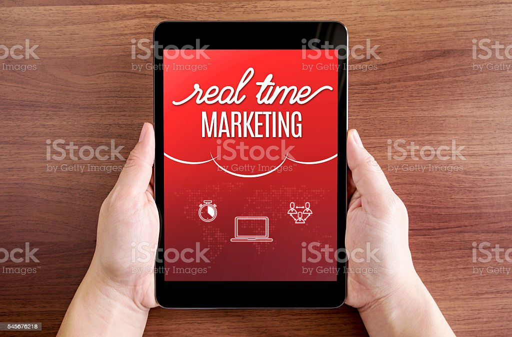 Two hand holding tablet with Real time marketing stock photo