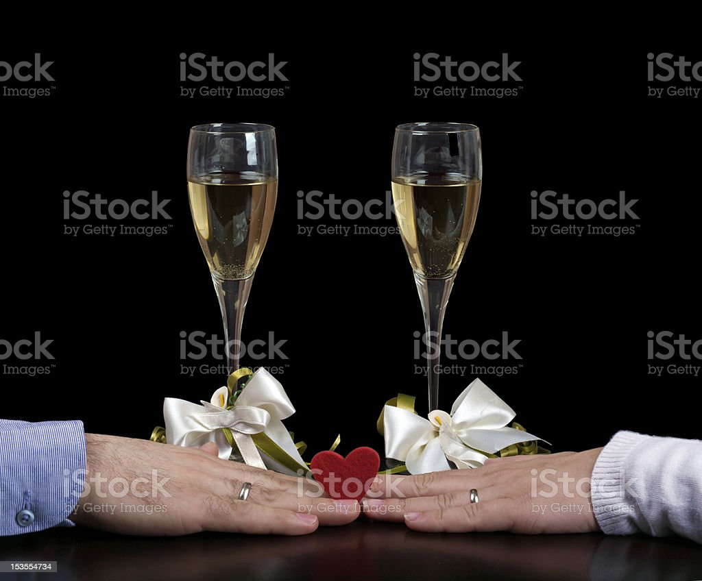 Two hands and red heart with wineglasses behind stock photo