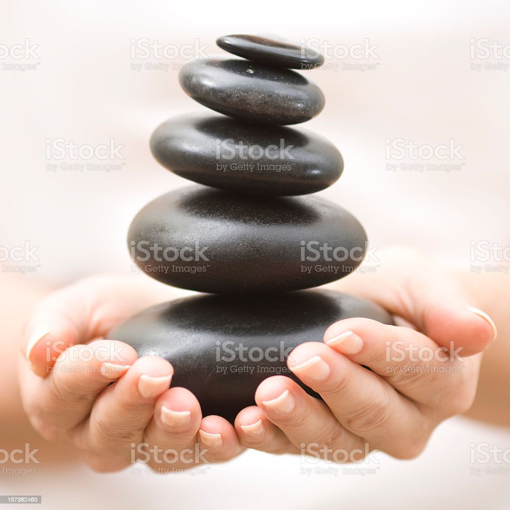 Two hands balancing a stack of black river rocks stock photo
