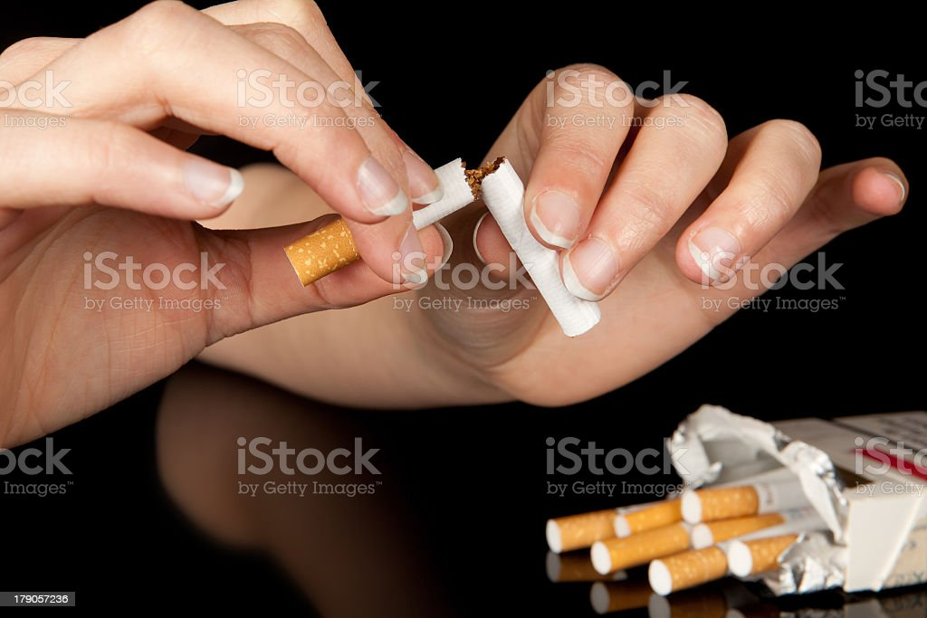 Two hands break a cigarette in half next to an open packet royalty-free stock photo