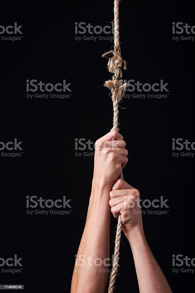 Two hands clinging hopelessly to a rope about to break stock photo