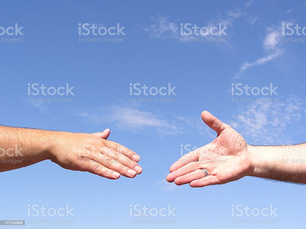 Two hands coming together for a handshake in front of sky stock photo