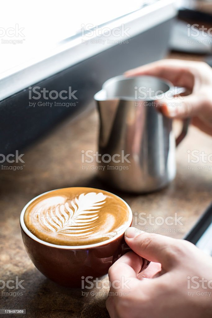 Two hands creating cappuccino froth art in a coffee shop stock photo