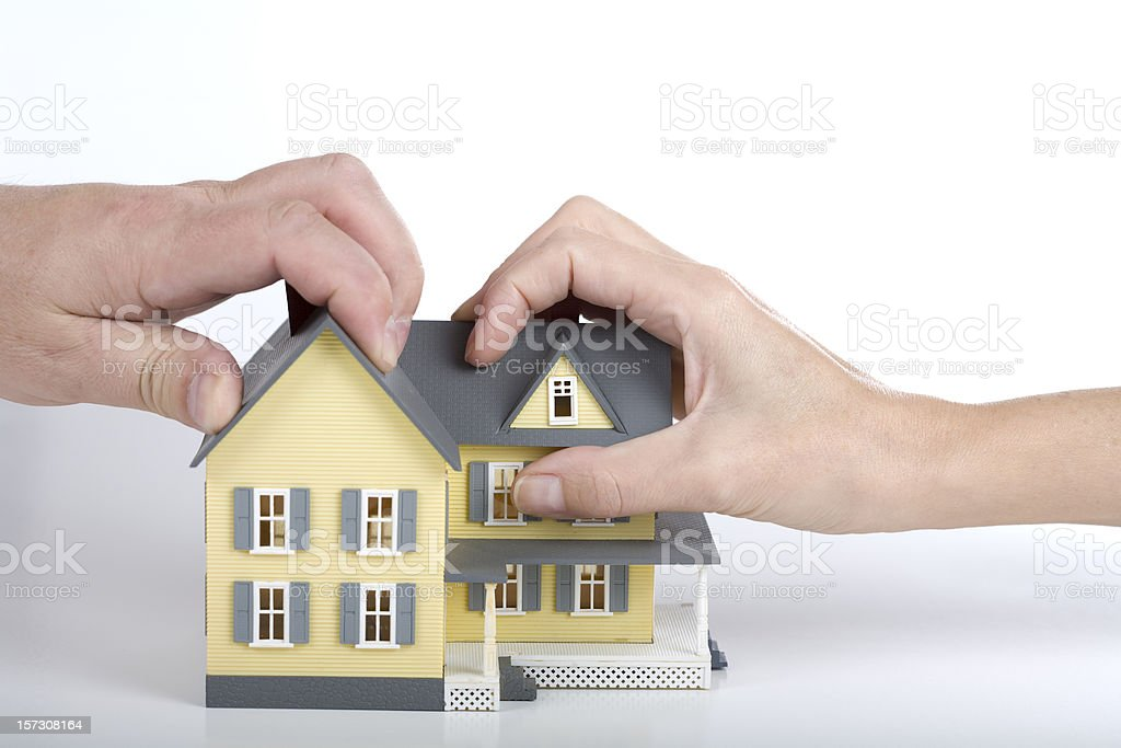 Two hands gripping a yellow model house with grey roof stock photo