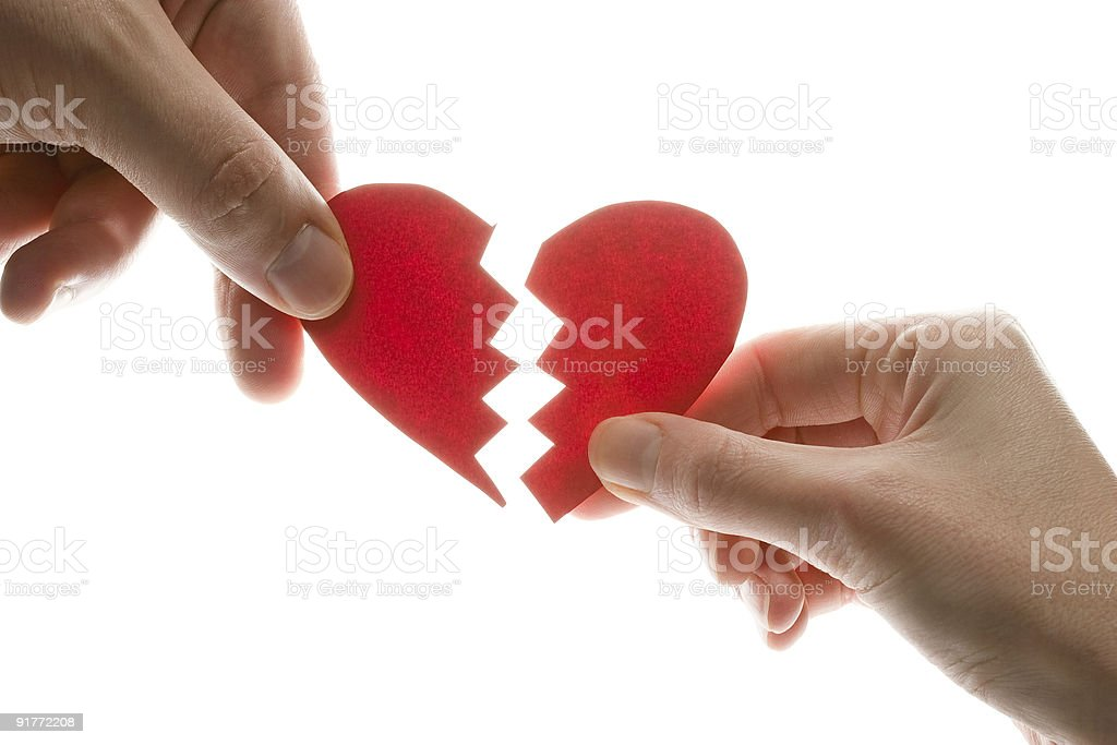 Two hands holding a broken heart stock photo
