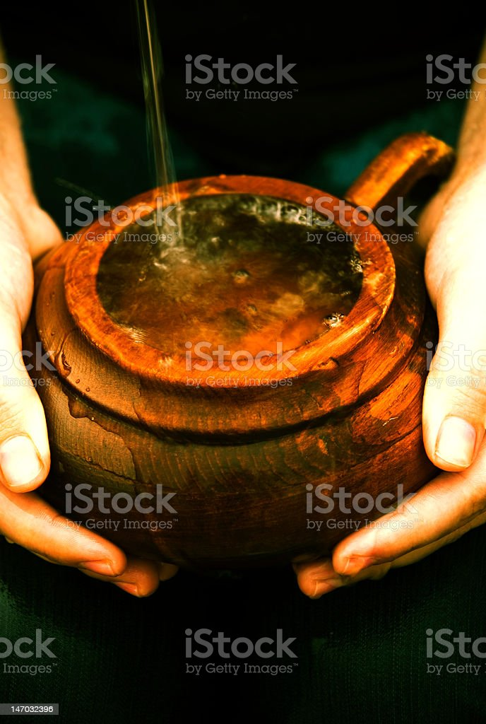 Two hands holding a cup overflowing with liquid stock photo
