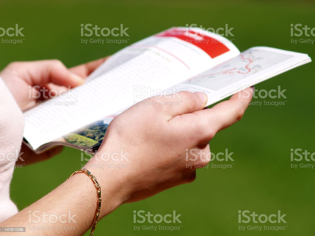 Two hands holding a guidebook with green background stock photo