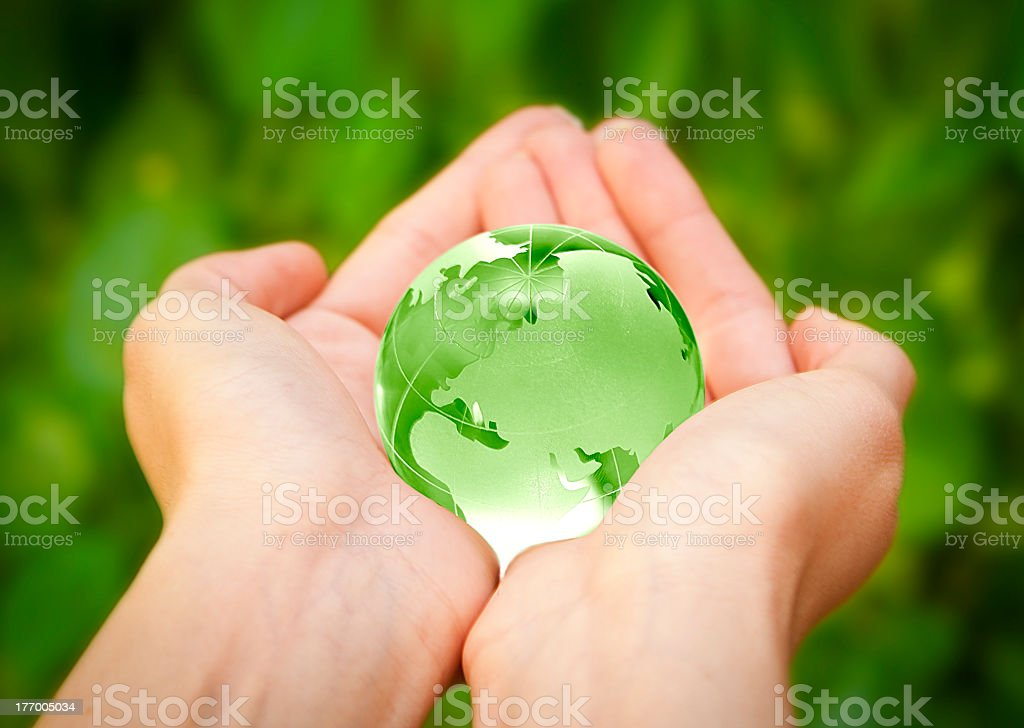 Two hands holding a small green globe against green backdrop stock photo