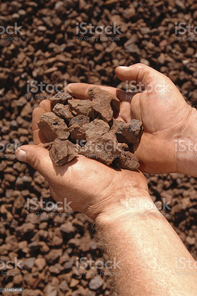 Two hands holding an iron ore sample. royalty-free stock photo