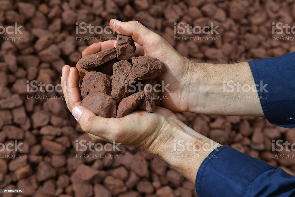 Two hands holding an iron ore sample. stock photo