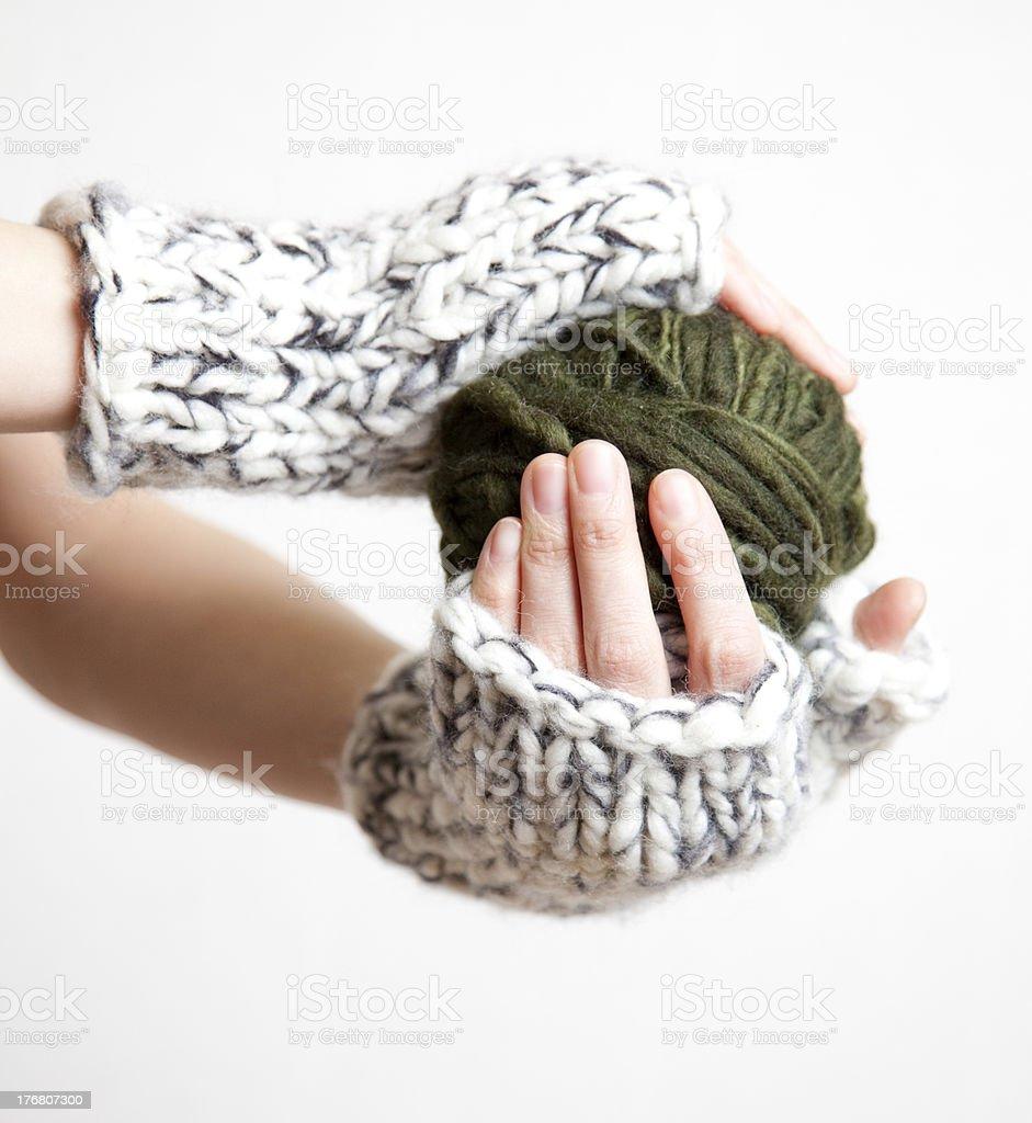 two hands holding ball of yarn, wearing chunky wrist warmers stock photo