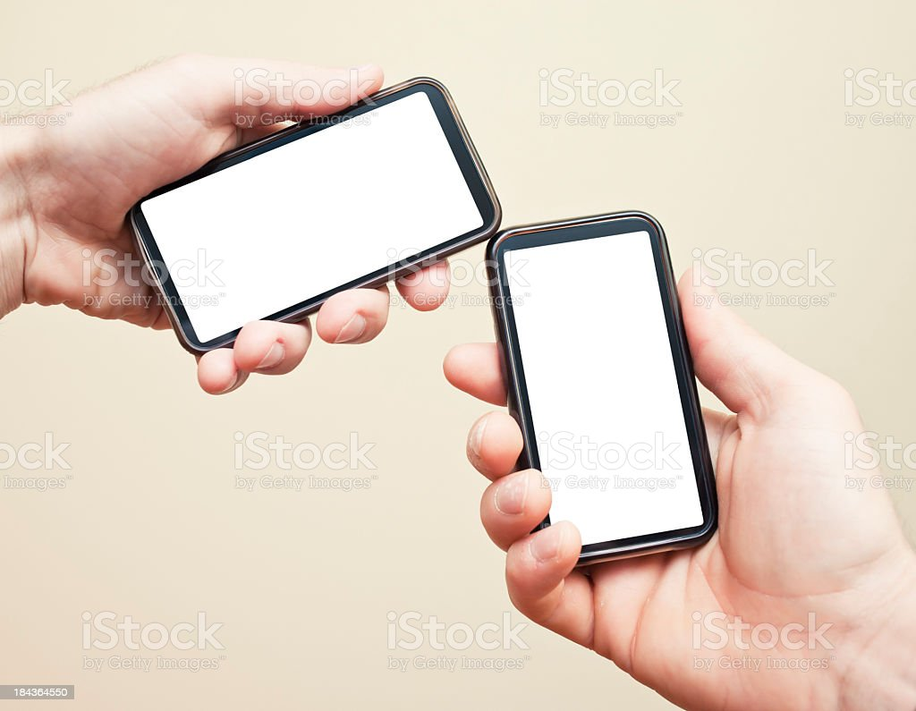 Two Hands Holding Connected Smart Phones royalty-free stock photo