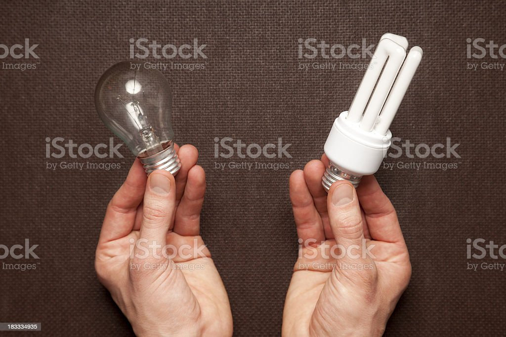 Two Hands holding Incandescent Lightbulbs and Engergy Efficient Lightbulbs royalty-free stock photo