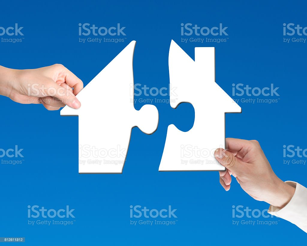 Two hands holding jigsaw pieces to finish house shape puzzle stock photo