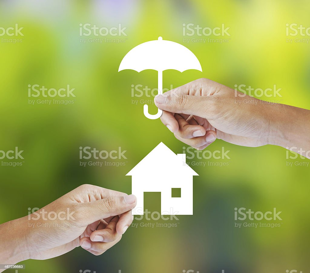 Two hands holding paper home and paper umbrella stock photo