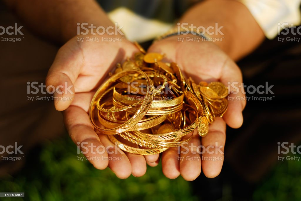 Two hands holding several golden bracelets royalty-free stock photo