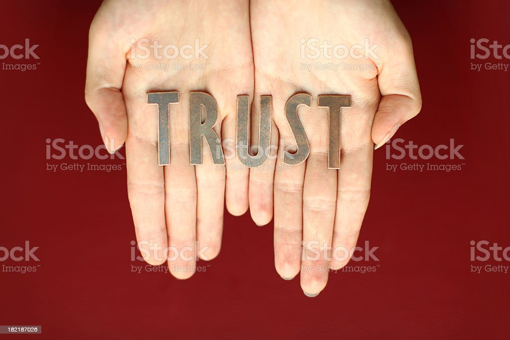 Two hands holding TRUST over red background royalty-free stock photo