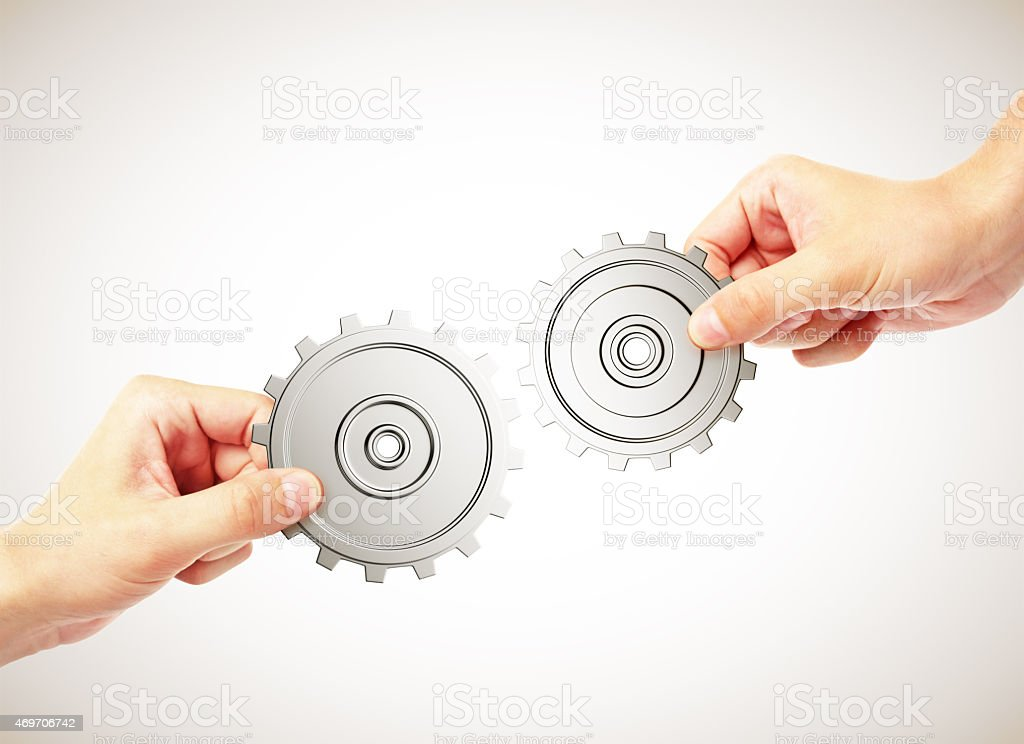 Two hands holding two gears together and connecting them stock photo