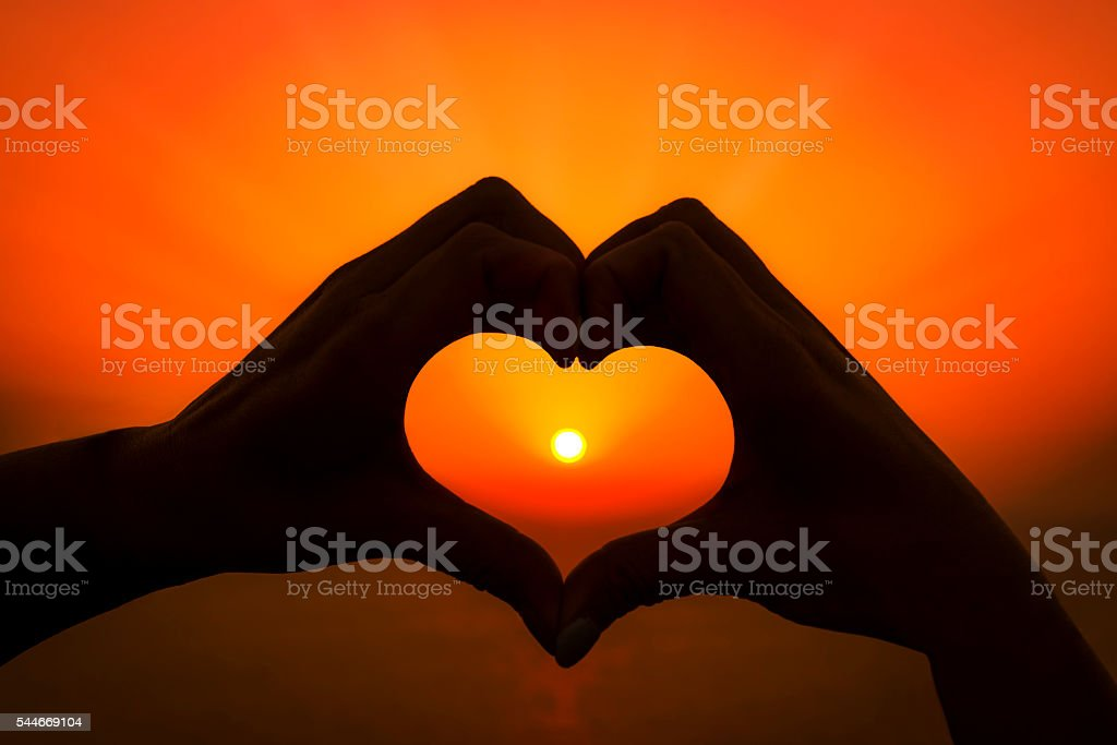 Two hands make a heart around the setting sun stock photo