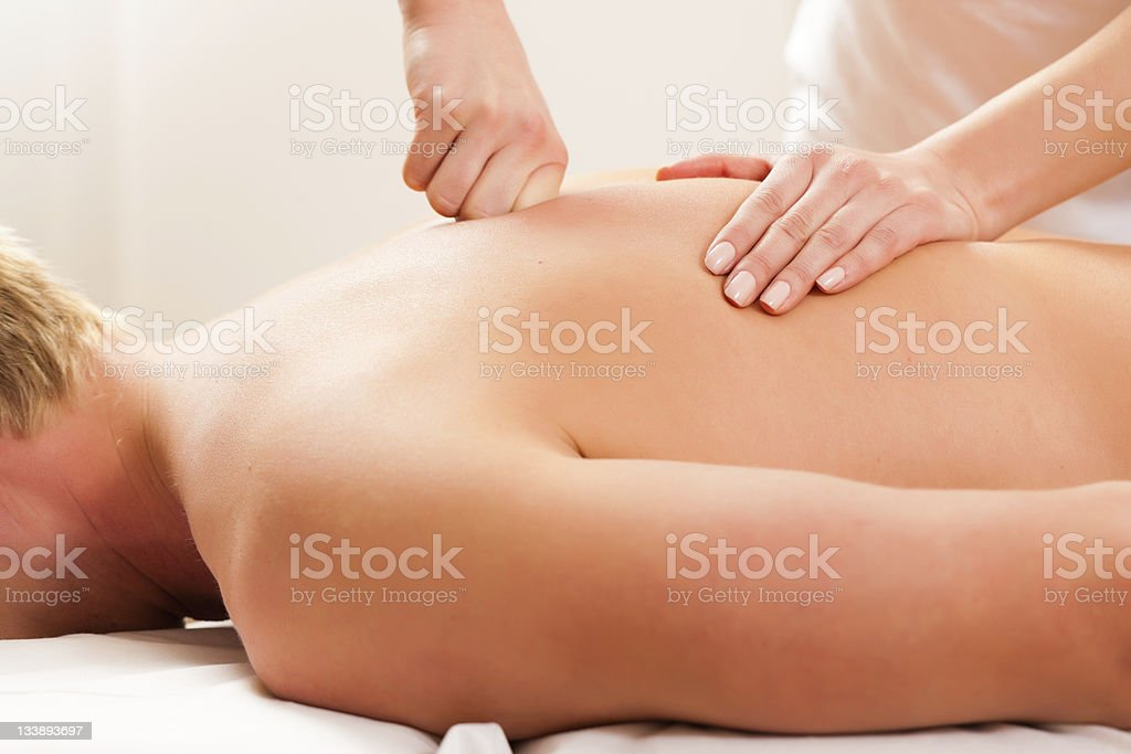 Two hands massaging physiotherapy patient lying on table royalty-free stock photo