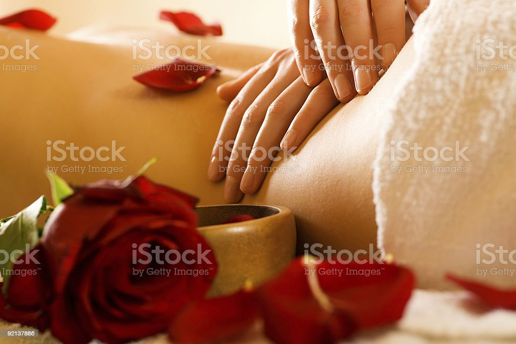 Two hands massaging small of naked woman's back with rose royalty-free stock photo