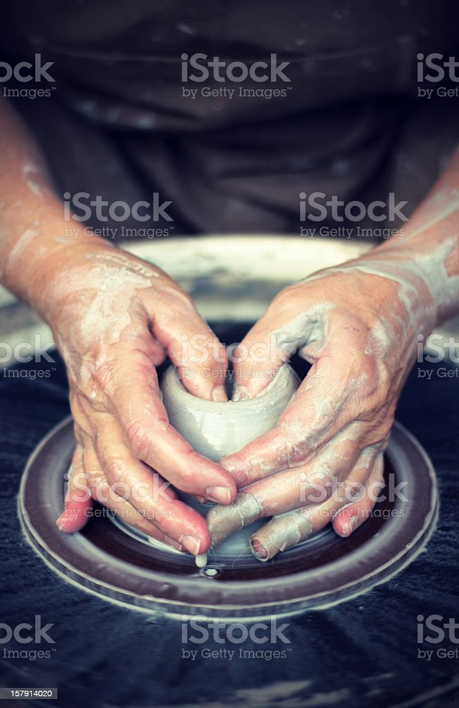 Two hands molding clay on a potters wheel stock photo
