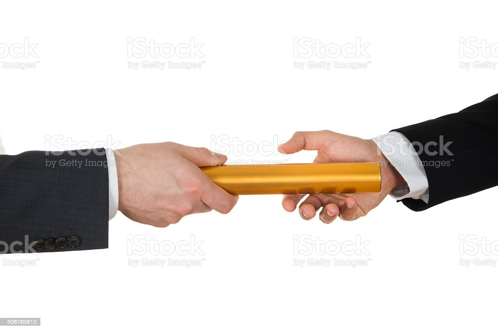 Two Hands Passing A Golden Relay Baton stock photo