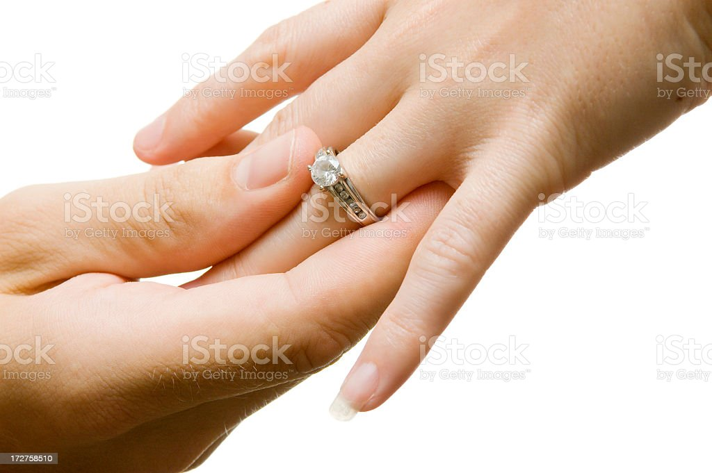 Two hands placing diamond ring on finger royalty-free stock photo