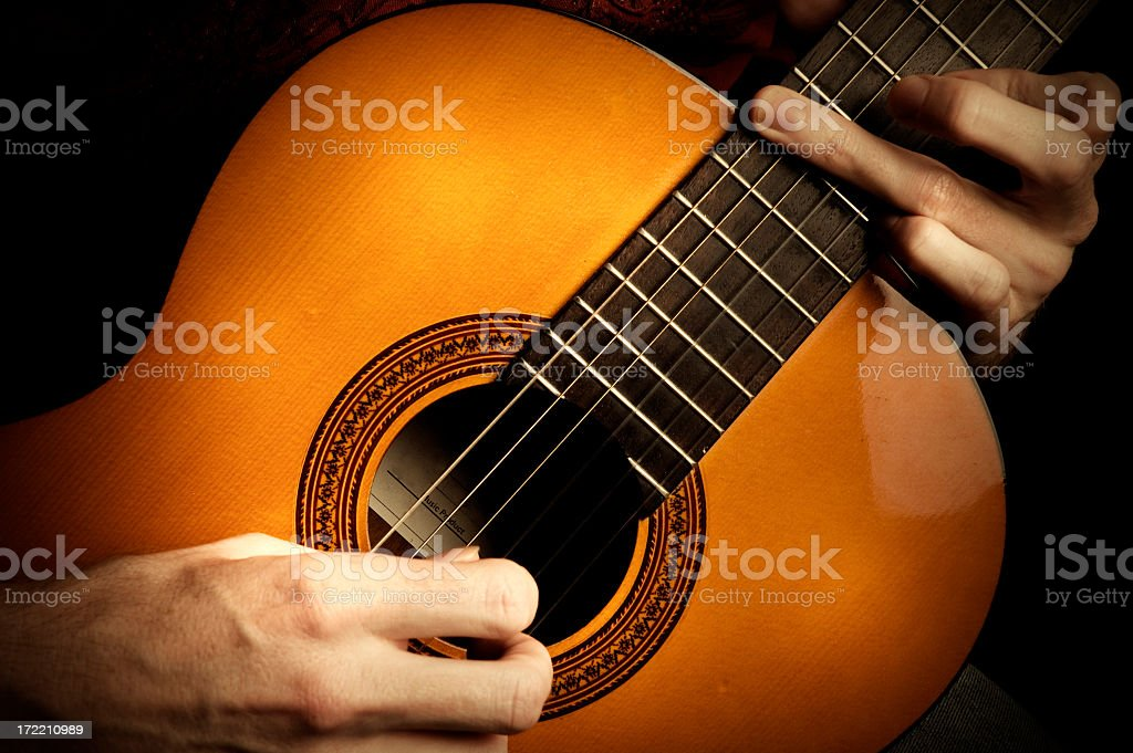 Two hands playing acoustic guitar stock photo
