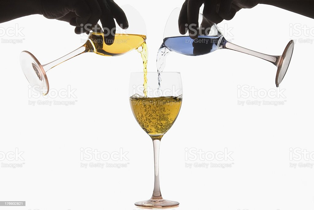 Two hands pouring different colored cocktails into a wine glass royalty-free stock photo