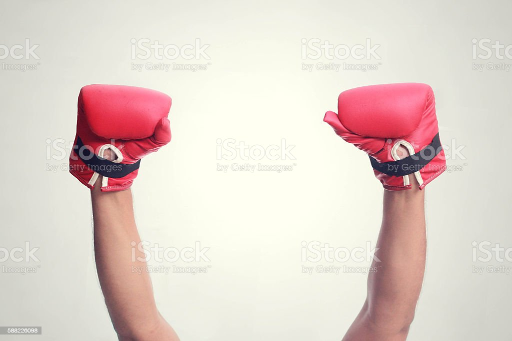 Two hands raised in the air wearing boxing gloves stock photo