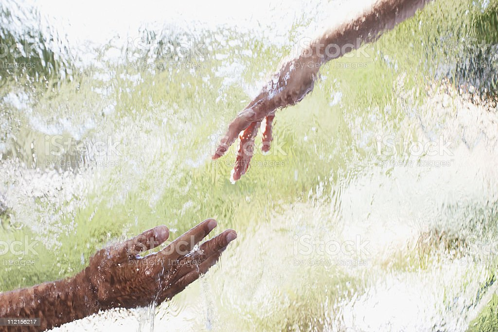 Two hands reaching out behind glass royalty-free stock photo