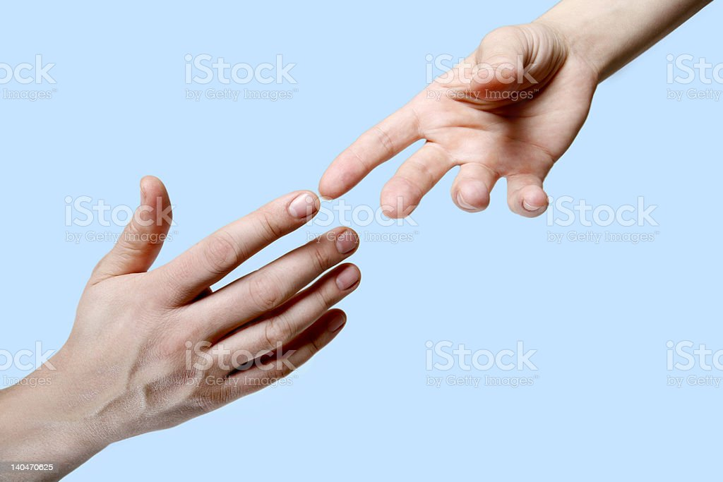 Two hands reaching out to touch fingers on a blue backdrop royalty-free stock photo