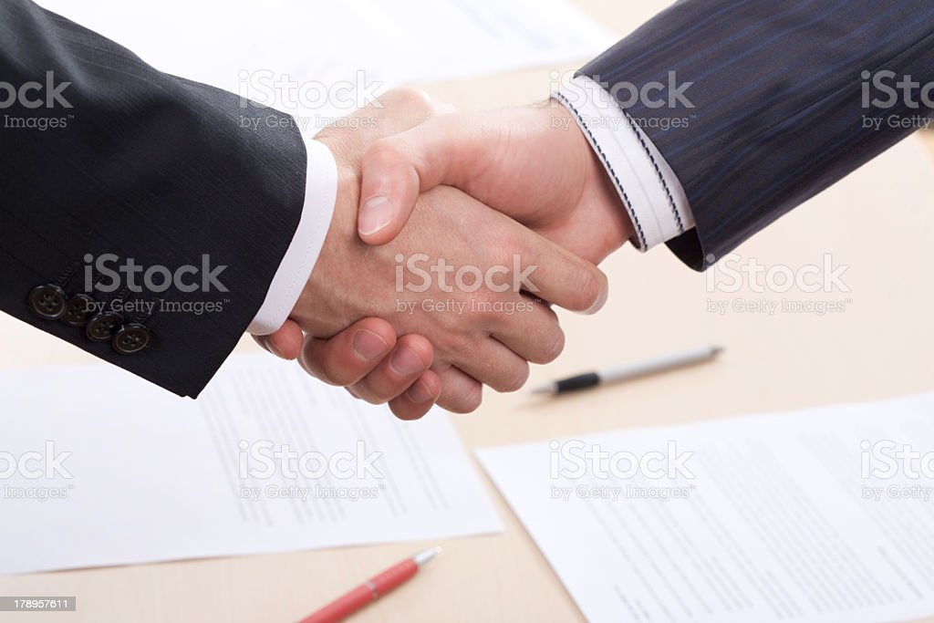 Two hands shaking over a business deal royalty-free stock photo