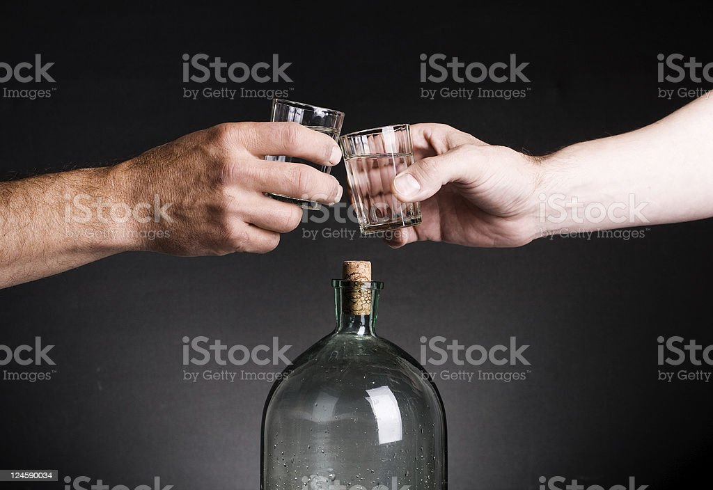 Two hands stamped glasses of vodka royalty-free stock photo